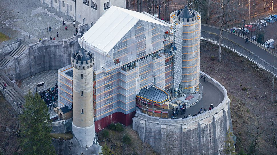 Zámek Neuschwanstein: V rámci plynulých sanačních opatření bylo okolo východní brány postaveno lešení PERI UP Rosett Flex, přičemž dočasné ochranné zastřešení překlenuje přístup k zámku.