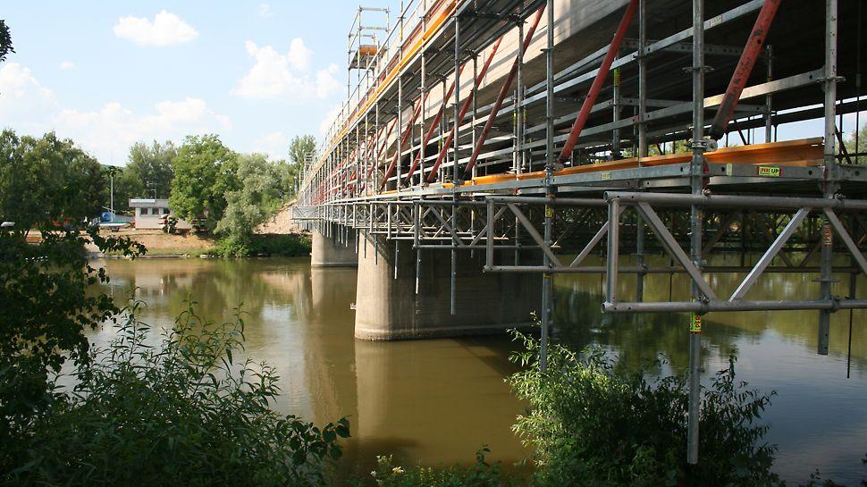 Podmienkou rekonštrukcia starého mosta v Trenčíne na Ostrov bolo aby ostal v neustálej prevádzke, preto PERI navrhla v mieste vodnej hladiny Váhu zavesenú pracovnú podlahu vo výške cca. 2,00 m pod spodnou hranou mostnej konštrukcie.