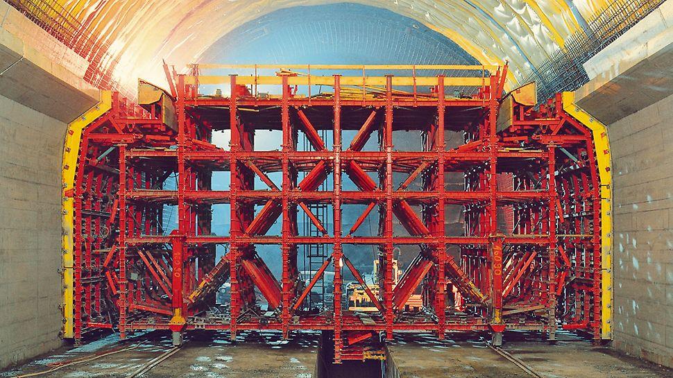 Tunel Lötschberg: Tunelový bednicí vůz pro průřez tunelu široký 15,74 m a vysoký 12,54 m. Nejdříve probíhalo bednění a betonáž bočních stěn.