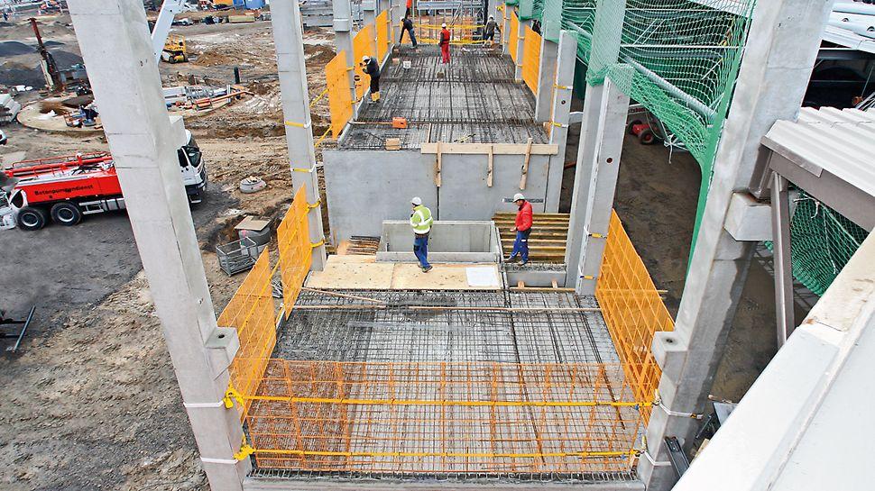 Die raumhohe Absturzsicherung wird mit Spanngurten an aufgehenden Bauteilen befestigt. Das Bauwerk bleibt unbeschädigt.