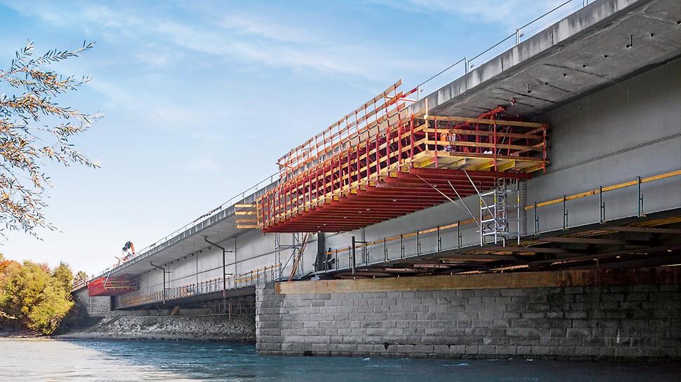 Zavěšený římsový vozík je připevněn ke spodní straně mostovky prostřednictvím kolejnic a závěsných rolen. Most je volně přístupný; provoz zůstává nenarušen.