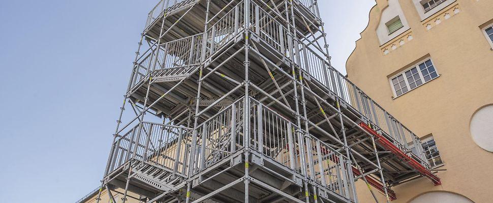 PERI Gerüsttreppen als temporäre Fluchttreppen: Während eines Umbaus dient dieser 14 m hohe Treppenturm als Fluchtweg. VARIOKIT Systembauteile tragen den Übergang zum Gebäude.