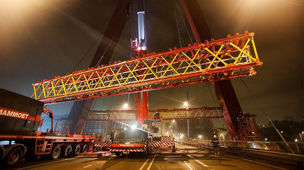 Knapp 40 m Fahrbahnüberbrückung: Über Nacht werden die 21 m langen, vormontiert angelieferten VARIOKIT Rüstbindereinheiten mit einem Mobilkran auf VST Stütztürme eingehoben und gekoppelt. Morgens um 6 Uhr kann die Brücke für den Verkehr wieder freigegeben werden.