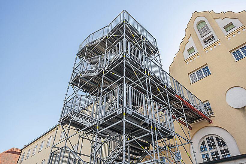 Pendant les travaux de rénovation, cette tour d'escalier de 14 m de haut sert d'issue de secours. Les composants du système VARIOKIT facilitent le transfert vers le bâtiment.