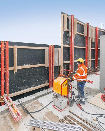 Arbeiter lässt RCS Schutzwandeinheit mithilfe der mobilen RCS Kletterhydraulik in die gewünschte Höhe entlang der Kletterschinen klettern.
