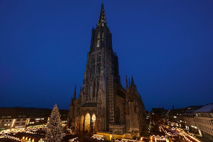 Ulmer Münster und der am Fuße der Kirche leuchtende Ulmer Weihnachtsmarkt bei Nacht.