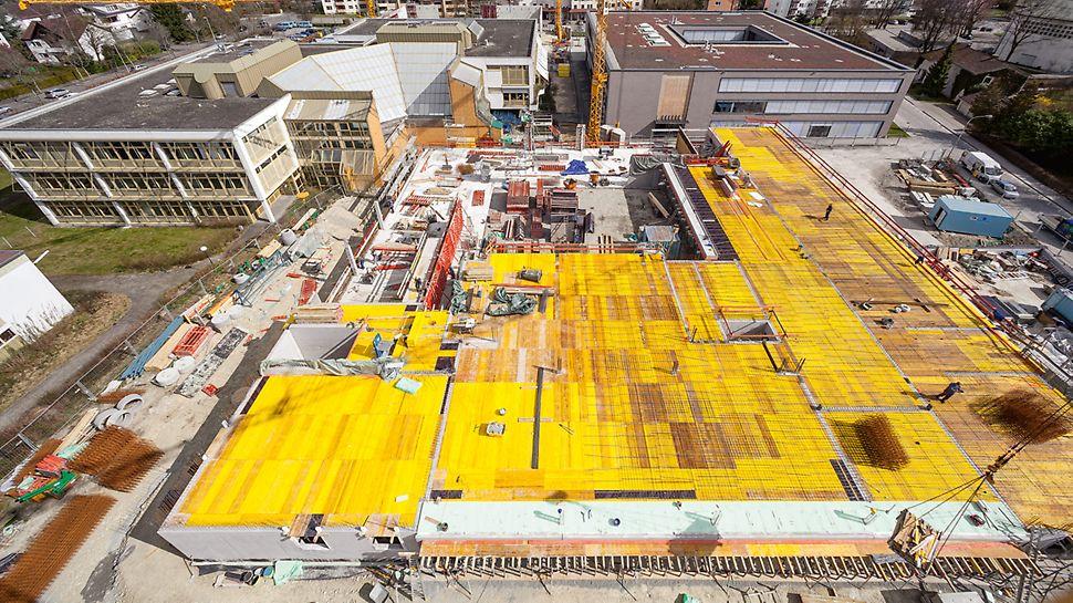Luftaufnahme der Baustelle sowie des bestehenden Altbaus im Hintergrund