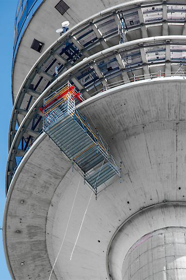 Mietbare Systembauteile des VARIOKIT Ingenieurbaukastens ermöglichen die Montage des vorab zu installierenden Schutznetzes und dient zum Abhängen des Hängegerüstes an der Kanzelunterseite in 152 m Höhe.