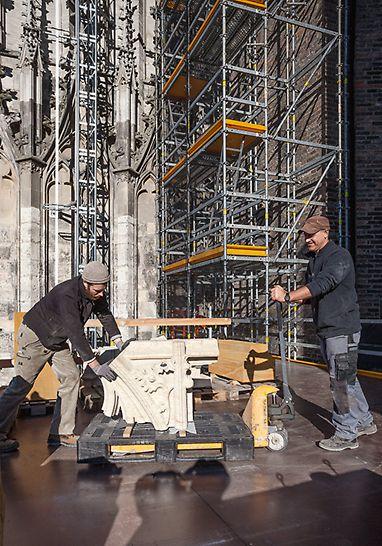 Zwei Männer transportieren auf der PERI UP Plattform einen schweren Stein mit Ornamenten, welcher im Bauwerk des Ulmer Münsters ausgetauscht werden soll.