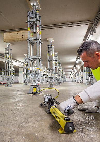 """Tiefgaragensanierung der Parkgarage """"Lechstraße"""" in Landsberg. Arbeiter bedient Hydraulikeinheit zum Vorspannen und Absenken der PERI UP Flex Schwerlaststütze HD"""