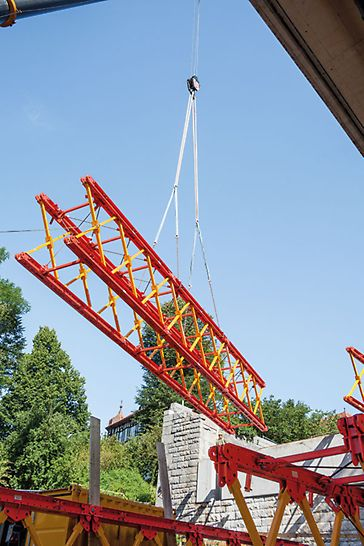 Mur Bridge Frohnleiten - Modular shoring assembly: VARIOKIT system components were pre-assembled on the ground to form truss segments and placed into intermediate storage with the crane. Three such segments were subsequently coupled to create a 37 m long truss unit and lifted over the Mur by means of a mobile crane.