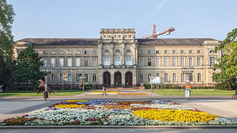 Front des Karlsruher Naturkundemuseums. Während auf dem Weg im Vordergrund eine Passantin läuft, kann man im Hintergrund einen Kran hinter dem Gebäude aufragen sehen.