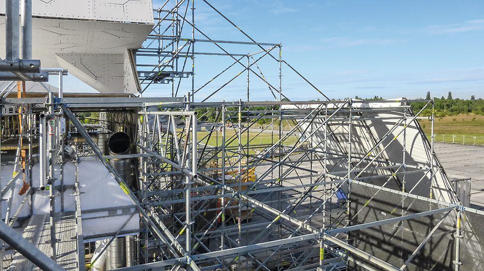 Festival Let it roll, Milovice: Částečné zakrytí vrchní části konstrukce a postranní věže pomocí vysunutí s diagonál a příhradových vazníků.