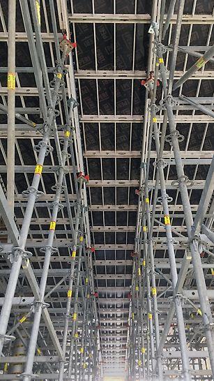 Kikvorsperspectief van de SKYDECK vloerbekisting boven de inkomhal op 6m50 hoogte, ondersteund door een PERI UP steiger met speciaal door PERI ontwikkelde valkopsystemen.