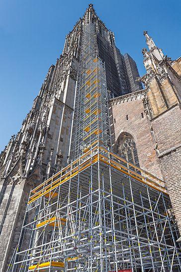 Hohes PERI Gerüst an der Fassade des Ulmer Münsters vom Münsterplatz aus betrachtet.