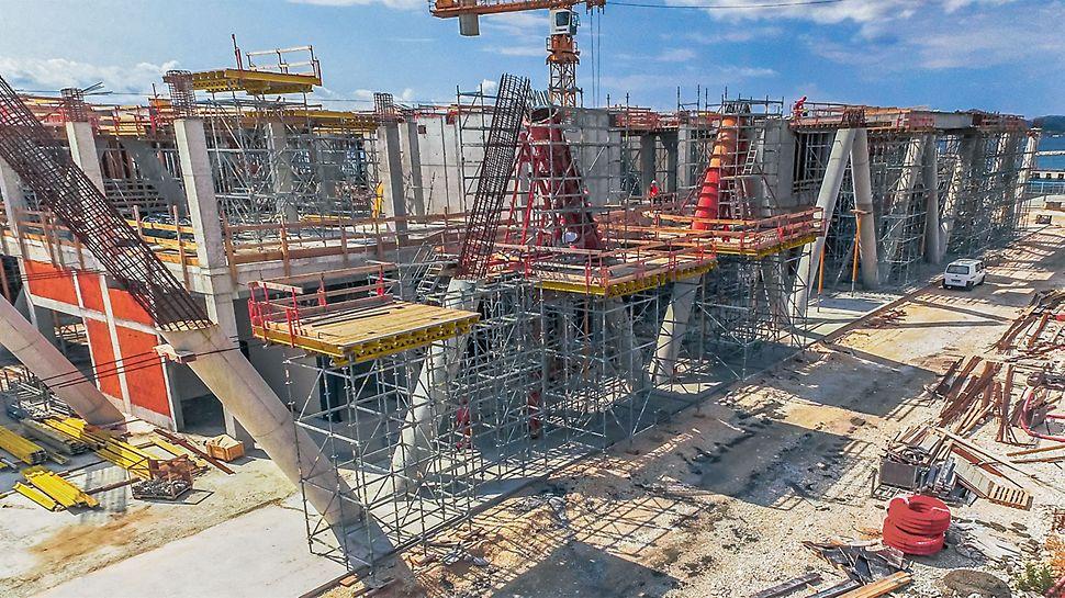 Zum Betonieren des zweiten Abschnitts der 10,30m hohen Säulen wurde mit dem PERIUP Flex Traggerüst eine Arbeitsplattform errichtet, die sich im 25-cm-Systemraster flexibel an die schräg im Raum verlaufenden Rundsäulen anpassen ließ.