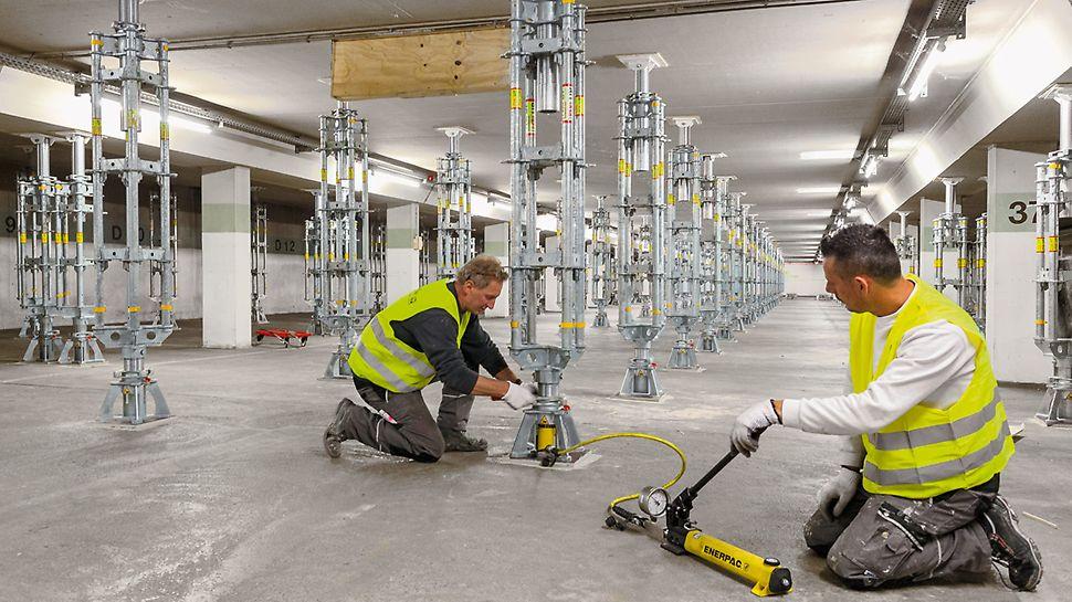 """Zwei Arbeiter, die bei den Sanierungsarbeiten in der Parkgarage """"Lechstraße"""" in Landsberg, die PERI UP Schwerlaststützen mit der Hydraulikeinheit montieren, vorspannen und absenken."""