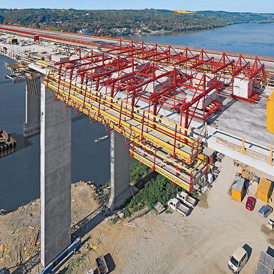 VARIOKIT φορείο σκυροδέτησης πεζοδρομίων γεφυρών: το φορείο που κινείται στο φορέα της γέφυρας μπορεί να προσαρμοστεί εύκολα σε κάθε εμπόδιο και μεταβολές στη διατομή. Όλες οι απαιτούμενες εργασίες προσαρμογής διεξάγονται από την πλατφόρμα εργασίας.