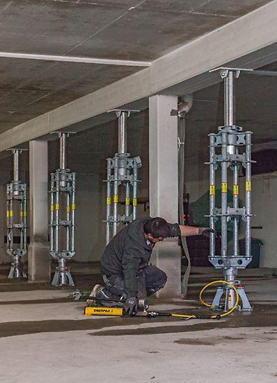 Arbeiter, der die PERI UP Absenkspindeln mithilfe von einer Hydraulikeinheit einstellt.