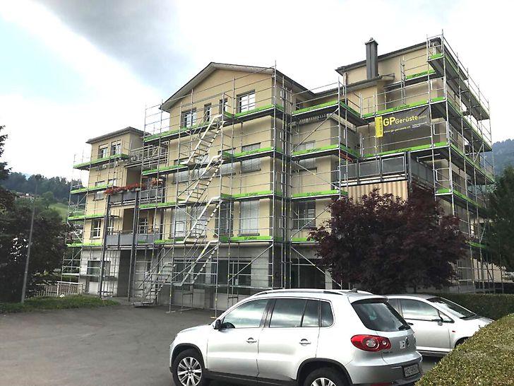 Westfassade, im Hintergrund das eingerüstete Gebäude, vorne parkierte Autos