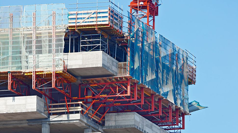 Auskragende VARIOKIT Fachwerke aus mietbaren Systemteilen tragen die hohen Frischbetonlasten der massiven, 28 cm starken Balkone mit 1,30 m hohen Brüstungen.