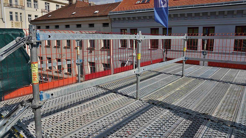 Horní podesta schodiště PERI UP s ochrannými mřížemi proti pádu z výšky PROKIT. Zajištění bezpečného pohybu po mostovce v Den otevření stavby.