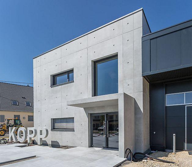 L'immeuble de bureaux moderne à deux étages se distingue par sa façade de béton apparent remarquable dotée d'un grillage de joints et de points d'ancrage nettement agencés.
