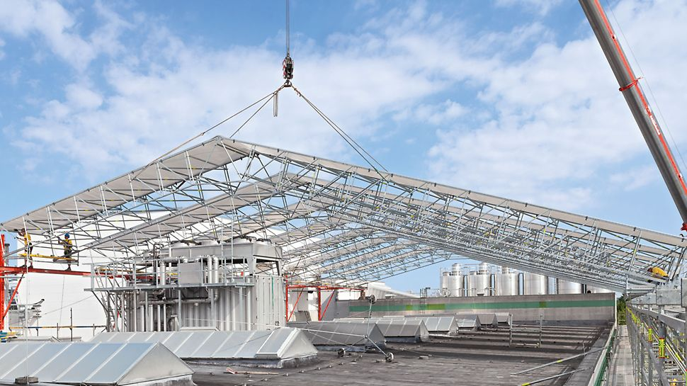 PERI UP Flex dak voor weersbescherming: De kraan hijst het volledige segment snel en veilig op zijn plaats nadat het op de grond gemonteerd is.