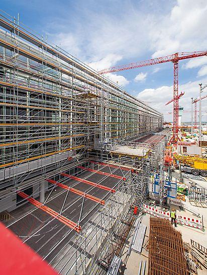 Satelitski terminal zračne luke München, Njemačka - PERI UP konstrukcija skele pouzdano razgraničava gradilišne tijekove i rad zračne luke. Istovremeno radnicima na fasadi služi kao radna skela. Stepenišni pristupi i široko napregnuta premošćivanja upotpunjuju rješenje skele stručnjaka iz Weißenhorna.