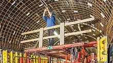 Pracovník stojící na bednicím vozíku provádí instalační práce na klenutém stropu.