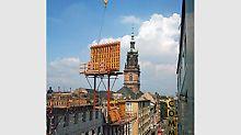 1973 erhöht das weltweit erste Klettergerüst die Sicherheit und das Arbeitstempo auf der Baustelle. Die kühne Konstruktion rationalisiert das Bauen hoher Gebäude erheblich, denn Schalung und Gerüst lassen sich in einem Kranhub umsetzen.