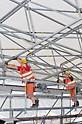 Arbeiter verschieben ein Bindersegment des PERI Wetterschutzdaches auf Rollen ohne maschinelle Hilfe.