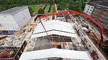 Geöffnetes Wetterschutzdach durch das der Arm des Kranes bis zu den aktuellen Baumaßnahmen und den Bauarbeitern gelangt.
