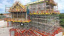Unidades de reticulados, montados con componentes estándar del sistema para obras de ingeniería VARIOKIT, sirven de apoyo para una cimbra PERI UP. Los tornapuntas para altas cargas permiten una adaptación óptima a superficies de apoyo inclinadas