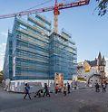 Baustelle des historischen Museums Frankfurt mit dem PERI UP Arbeitsgerüst im Einsatz. Vor der Baustellenabsperrung sieht man Passanten am Gebäude vorbei laufen.