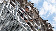 Arbeiter montiert die modularen Gitterträger ULS Flex von PERI am Gerüst vor dem Ulmer Münster.