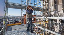 Frau steht auf einer hohen Etage des PERI UP Modulgerüsts. Sie hält einen Fotoapparat und fotografiert die Steinmetzarbeiten der Fassade des Ulmer Münsters.