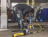 Arbeiter spannt eine der PERI UP Schwerlaststützen mithilfe einer Hydraulikeinheit vor.