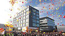 Aufsteigende Luftballons vor dem neuen Bürogebäude