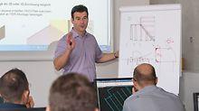 Seminarleiter hält Präsentation zur PERI Planungssoftware ELPOS und PERI CAD am Flipchart.