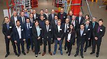 Gruppenbild von allen Teilnehmern, Betreuern und dem PERI Organisationsteam bei der 10. Endausscheidung der PERI Baubetriebsübung in der Ausstellungshalle der PERI Niederlassung in Weißenhorn.