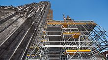 PERI UP nestles up to Ulm Minster - up to 71 m high - for the extensive renovation work. A 7 m high intermediate platform provides a possible storage location for the new stones.