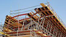 Die vorgefertigten VARIOKIT Bauteile der Stegaußen- und Kragarmschalung für den Überbau der Ortbetonbrücke wurden bereits auf dem Boden zusammengebaut, zeitsparend mit einem einzigen Kranhub angehoben und anschließend montiert.