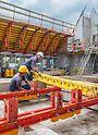 Zwei Arbeiter, die das Schalung und Tragsystem aus dem PERI Baukastensystemen VARIOKIT und PERI UP für das Schrägdach vorbereiten.