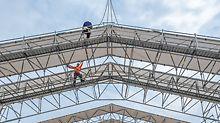 Das PERI LGS Wetterschutzdach mit zwei Arbeitern auf den Laufstegen - betrachtet aus der Froschperspektive.