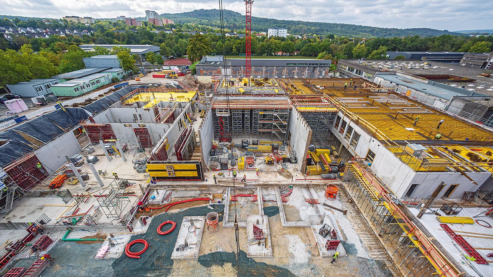 Das in massiver Stahlbetonbauweise zu errichtende, knapp 20 m hohe Schulgebäude weist Raumhöhen bis 8 m und Deckenstärken zwischen 28 cm und 36 cm auf.